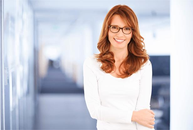 אשה עם משקפיים מחייכת מסתכל על הצופה במשרד