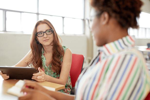 אשה עם טבלט בפגישה עם אשה במשרד