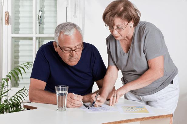 אשה מבוגרת עם משקפיים עוזרת לגבר עם משקפיים שיושב ועוברים יחדיו על מסמך