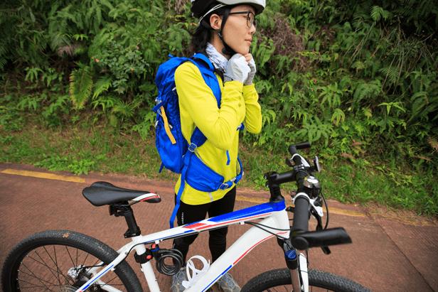 עדשות ספורט - אשה מהדקת את הקסדה לראש לפני שעולה על אופניי ספורט